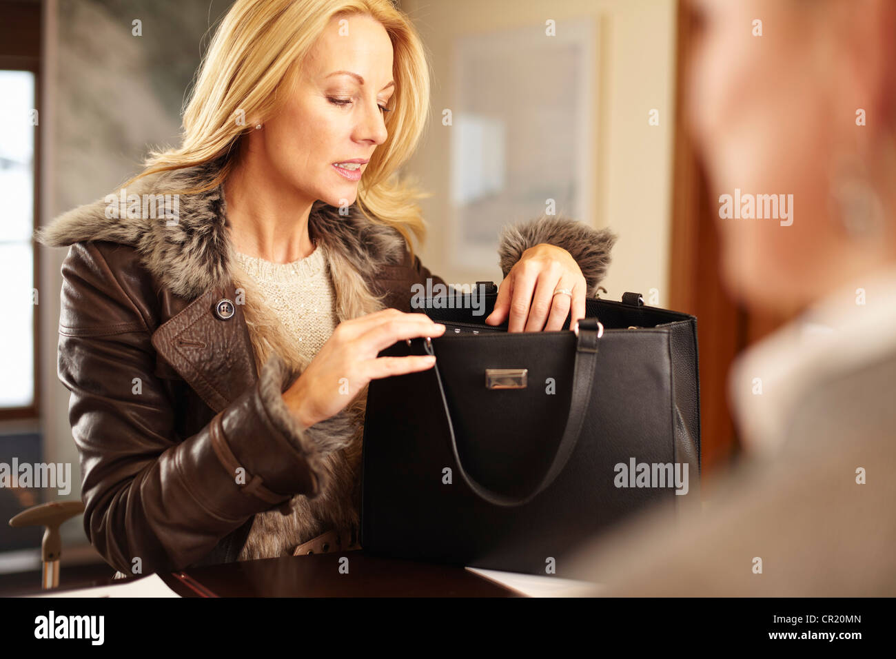 Woman rummaging through purse - Stock Image