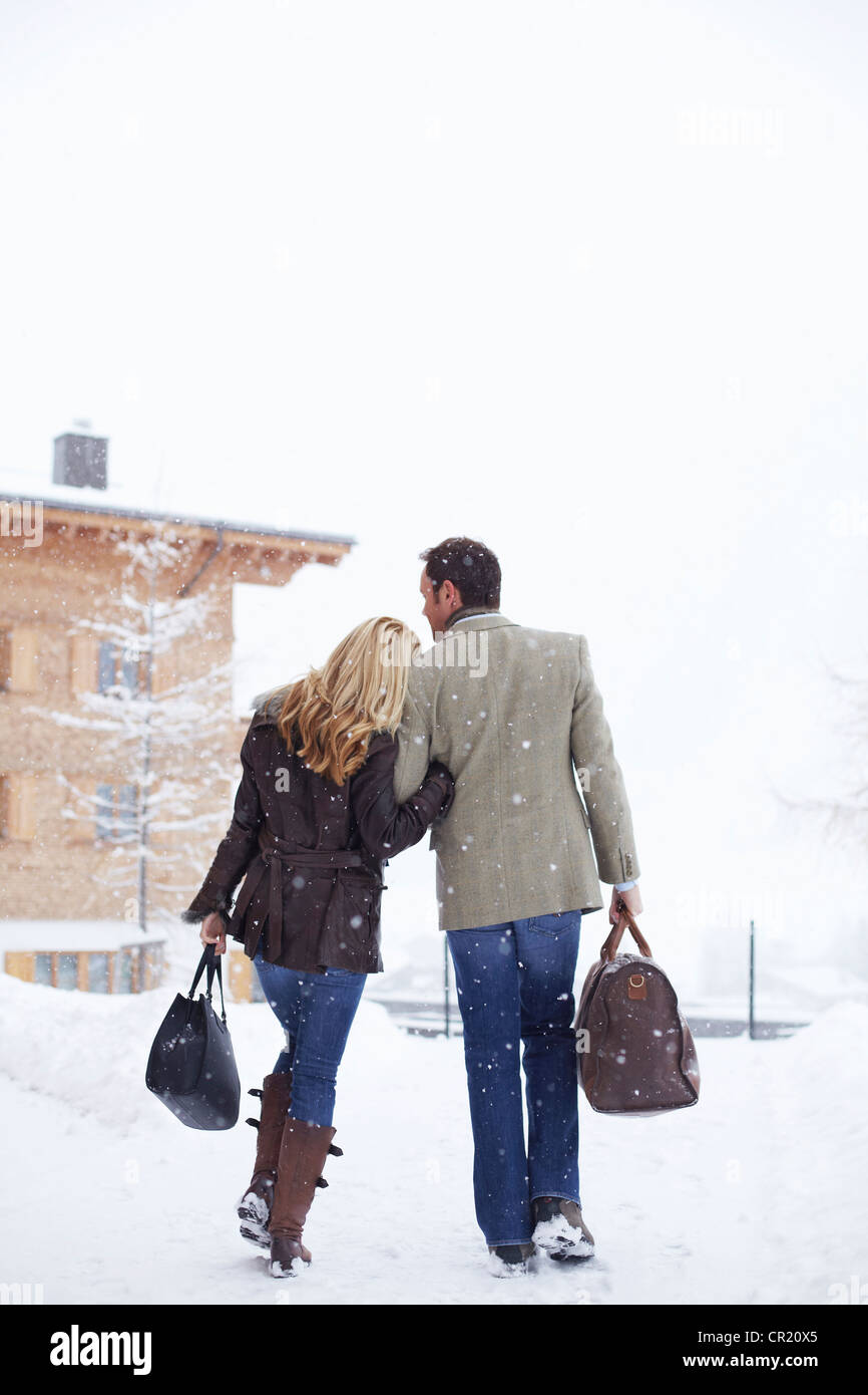 Couple walking together in snow - Stock Image