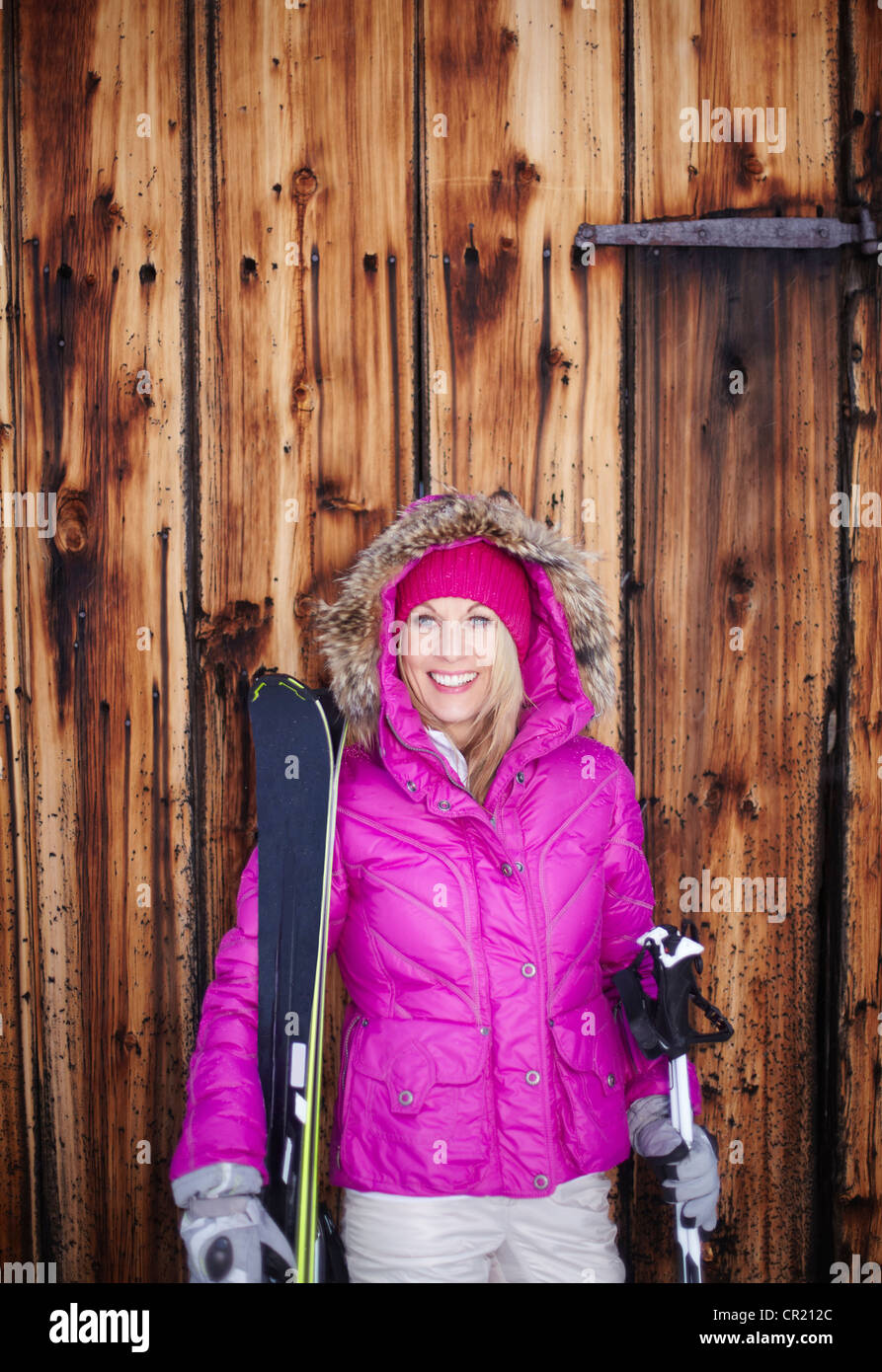 Woman standing with skis and poles - Stock Image
