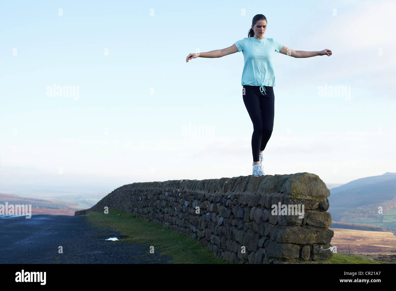 Runner balancing on rock wall - Stock Image