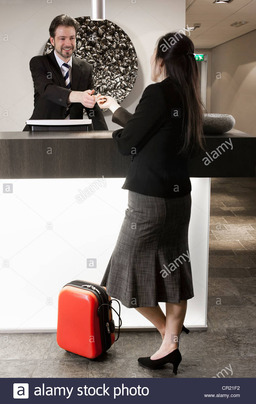 Businesswoman checking in to hotel - Stock Image