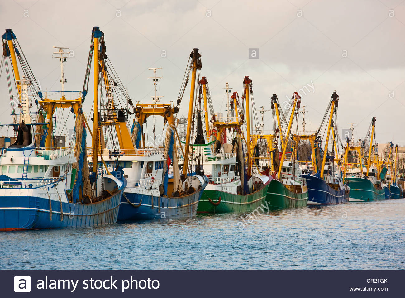 Trawler fleet docked at pier - Stock Image