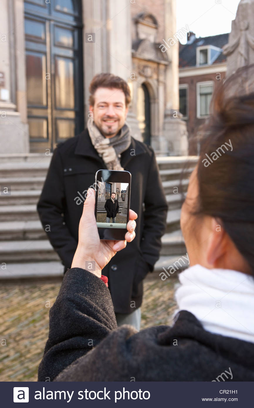 Woman taking picture of boyfriend - Stock Image
