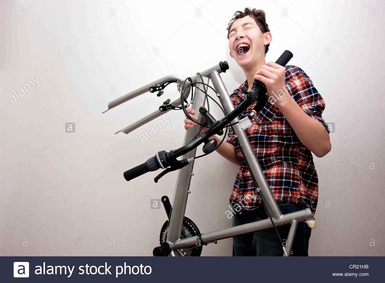 Laughing boy carrying bicycle parts - Stock Image