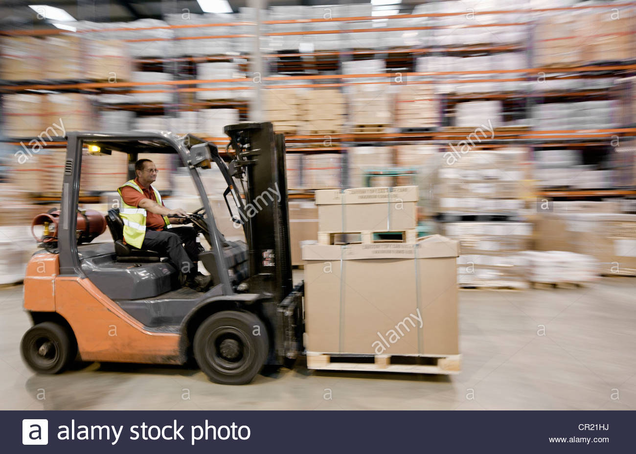 Blurred view of worker in warehouse - Stock Image