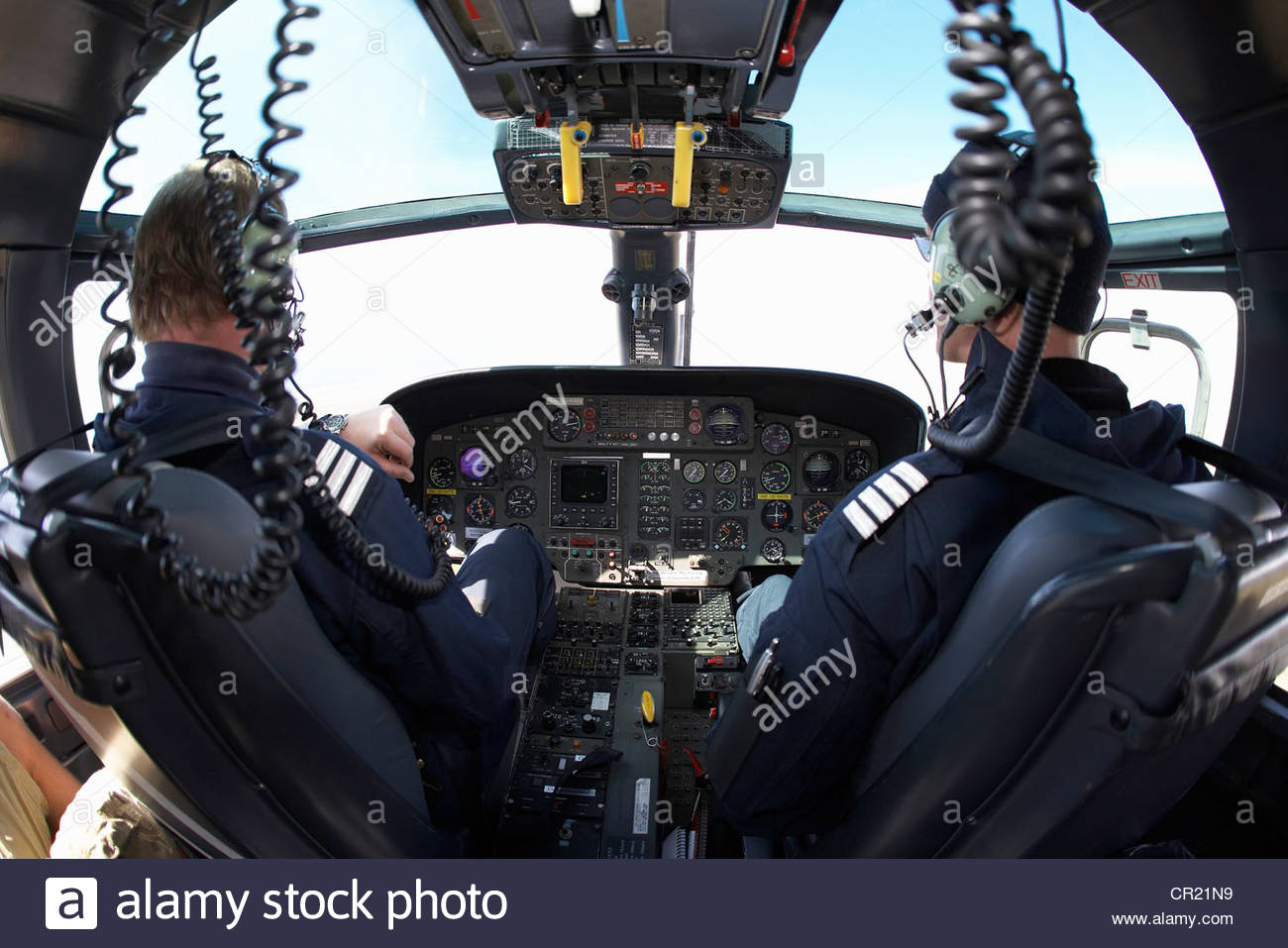 Helicopter pilots in cockpit - Stock Image
