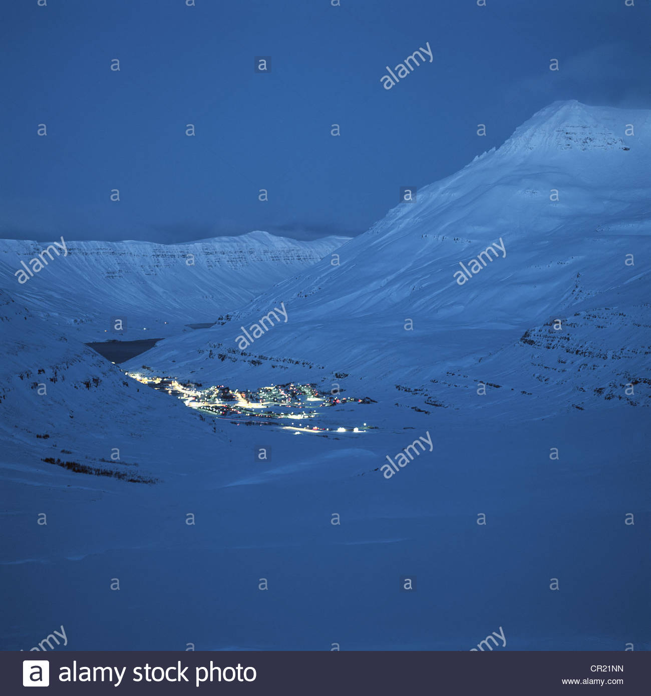 Snowy village lit up at night - Stock Image