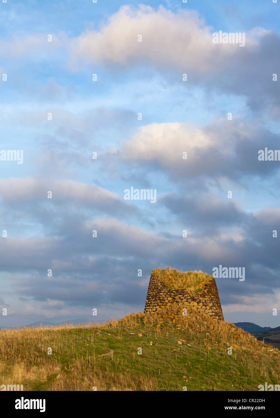 Stone structure on grassy hill - Stock Image