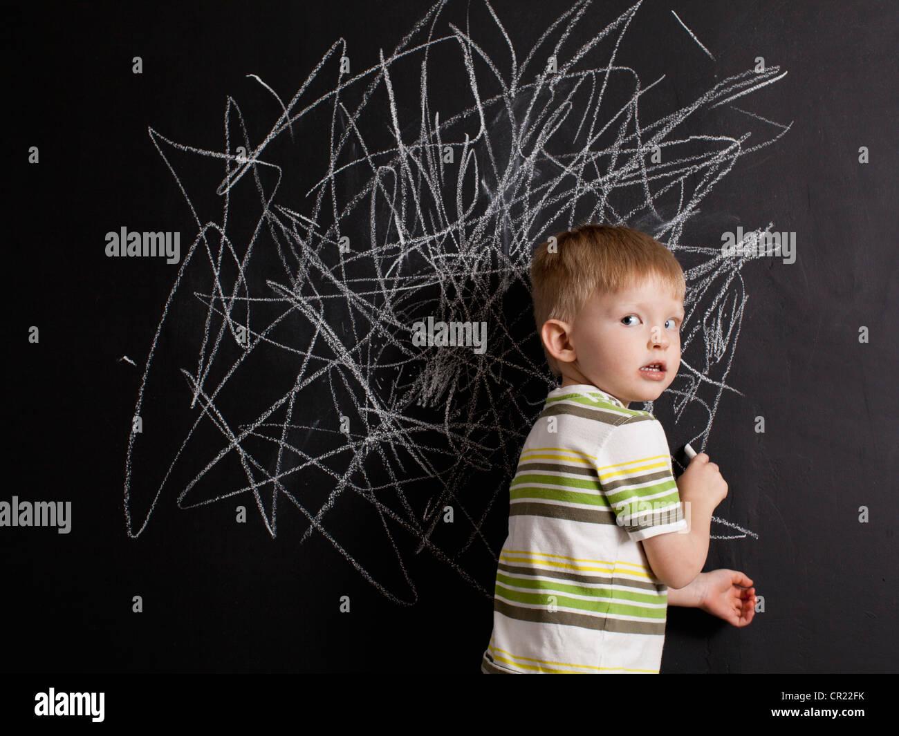 Cute toddler boy (2-3) standing against blackboard with daub written in chalk - Stock Image