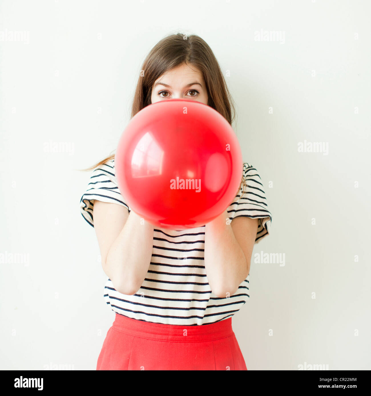 Studio shot of young woman blowing balloon - Stock Image