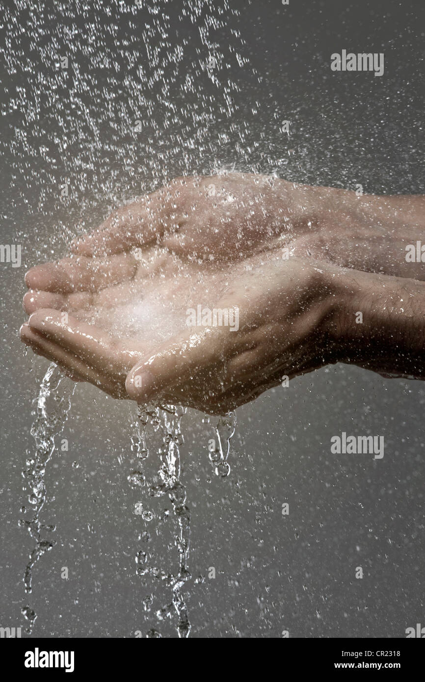 Woman catching water in cupped hands - Stock Image