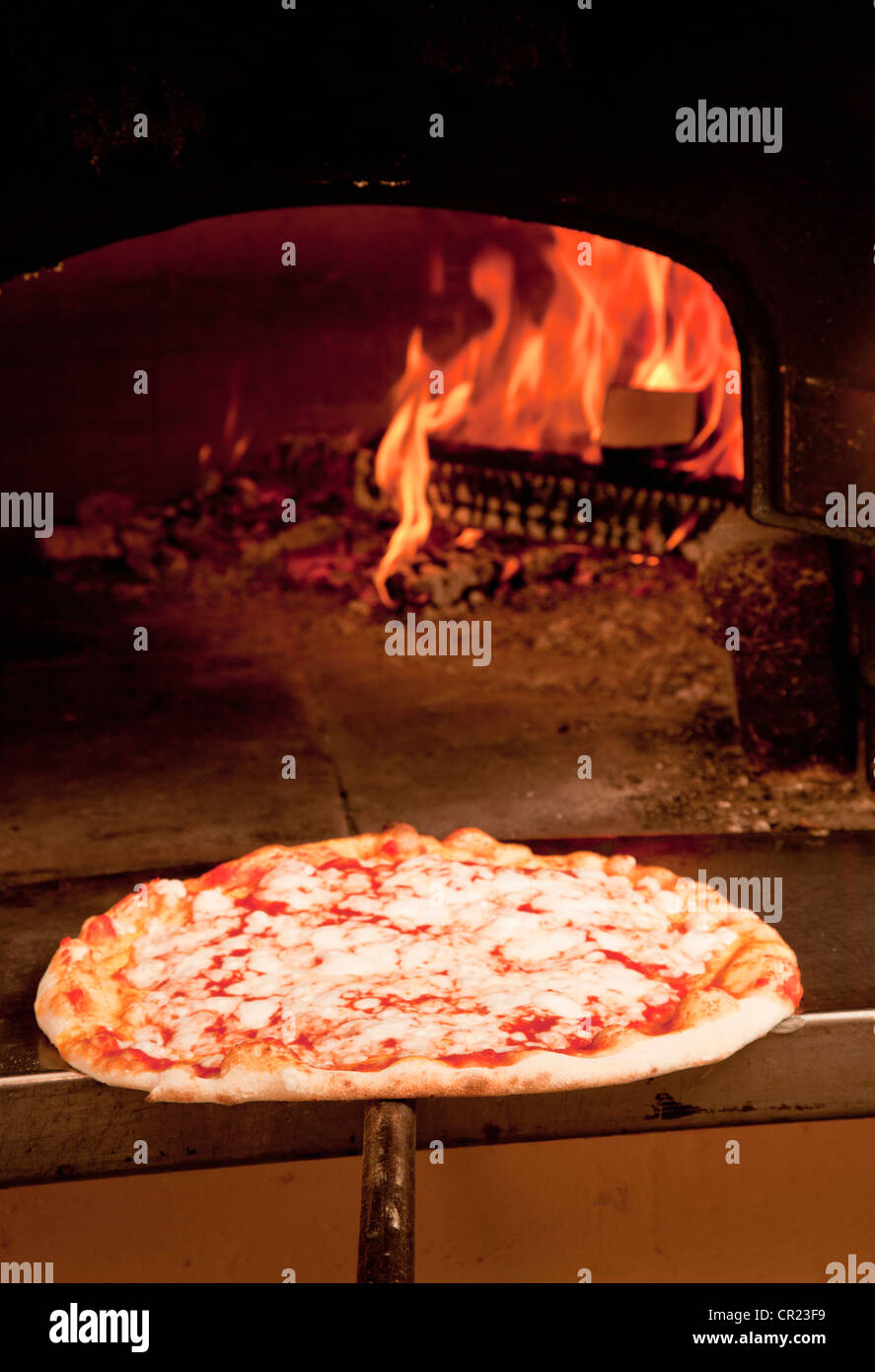 Chef pulling pizza from oven - Stock Image