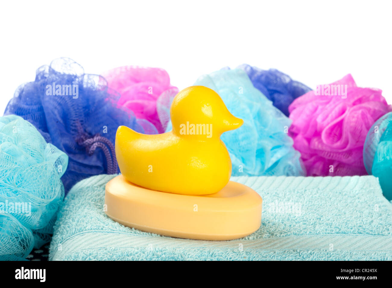A yellow duck shaped bar of shower soap on a light blue towel with shower poufs against a white background. - Stock Image