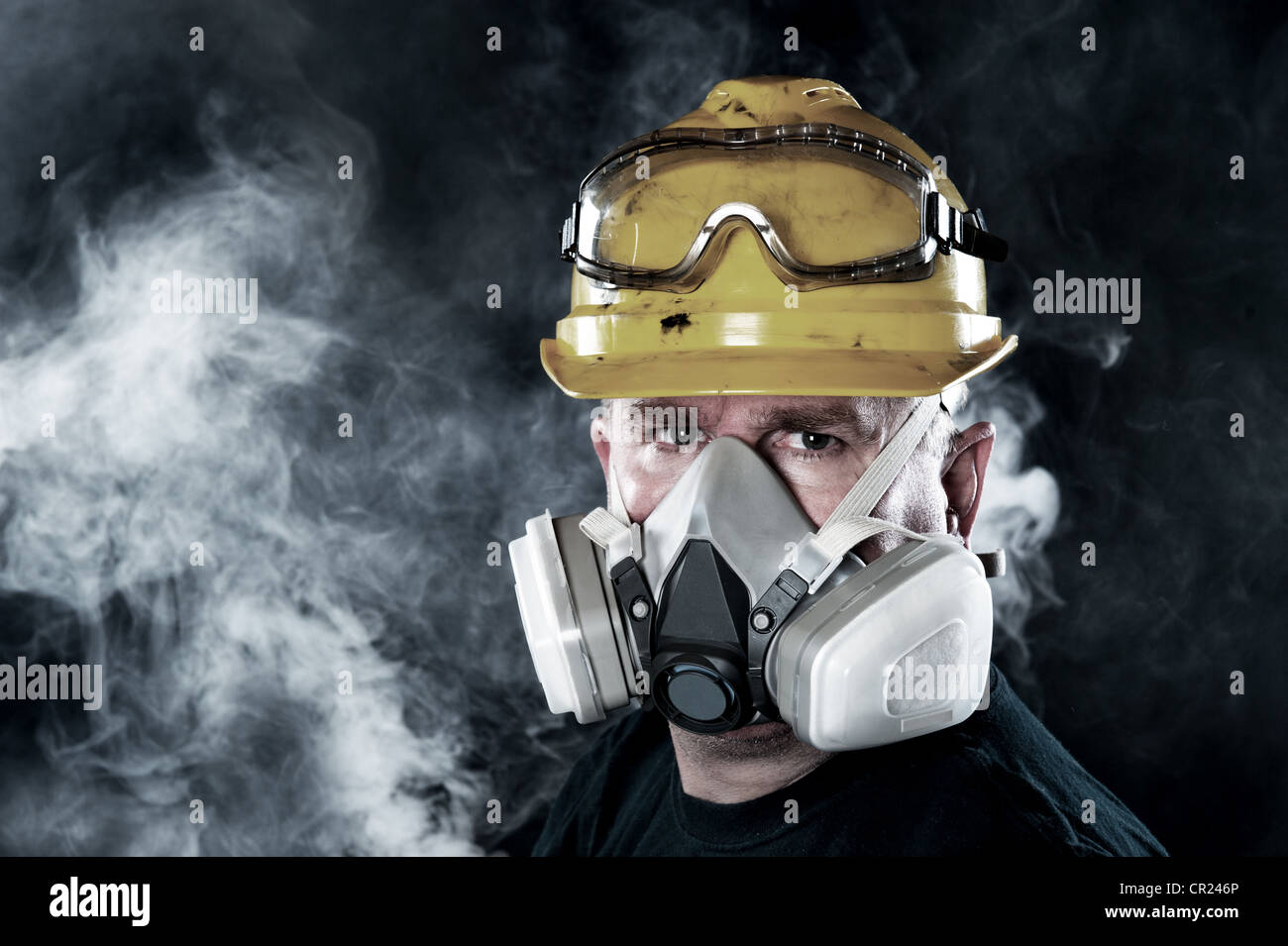 A rescue worker wears a respirator in a smokey, toxic atmosphere. Image show the importance of protection readiness - Stock Image