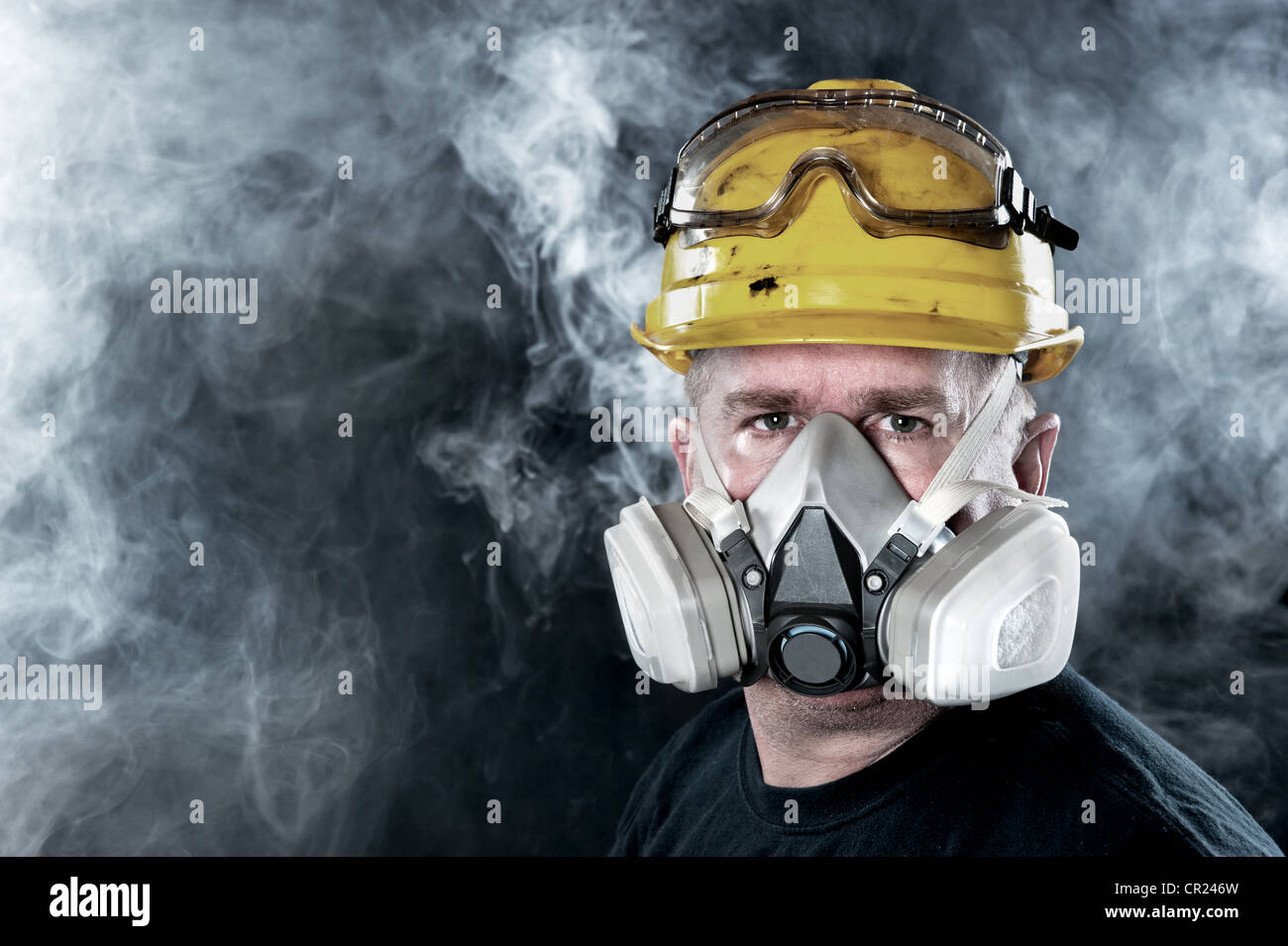 A rescue worker wears a respirator in a smoke, toxic atmosphere. Image show the importance of protection readiness - Stock Image