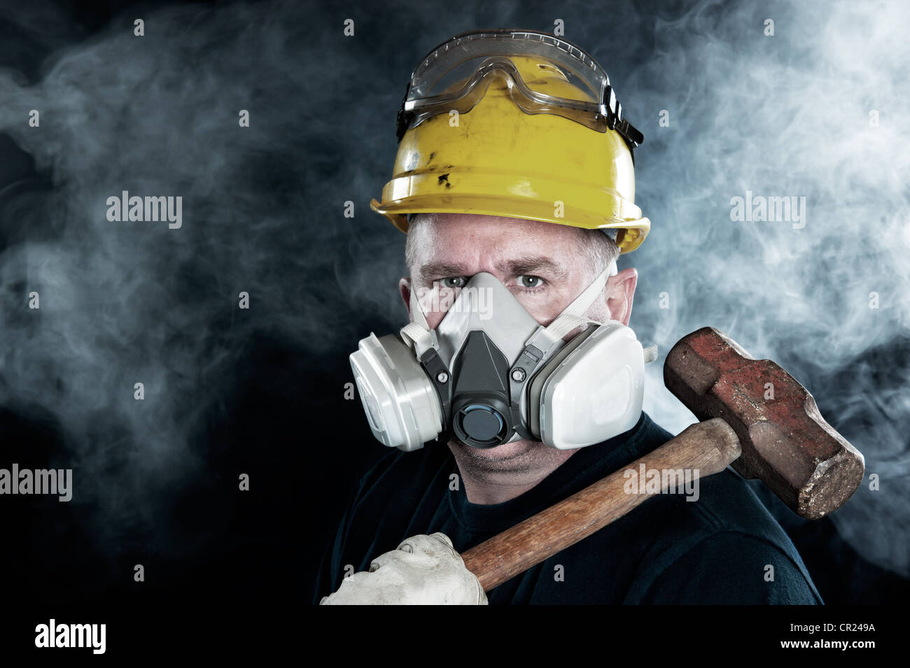 A rescue worker wears a respirator in a smoky, toxic atmosphere carrying a sledgehammer. - Stock Image