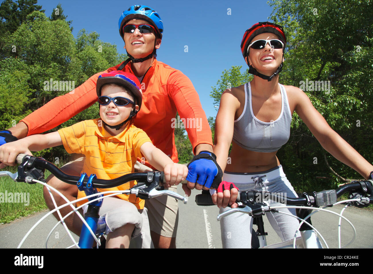 Portrait of happy family on bicycles in the park Stock Photo