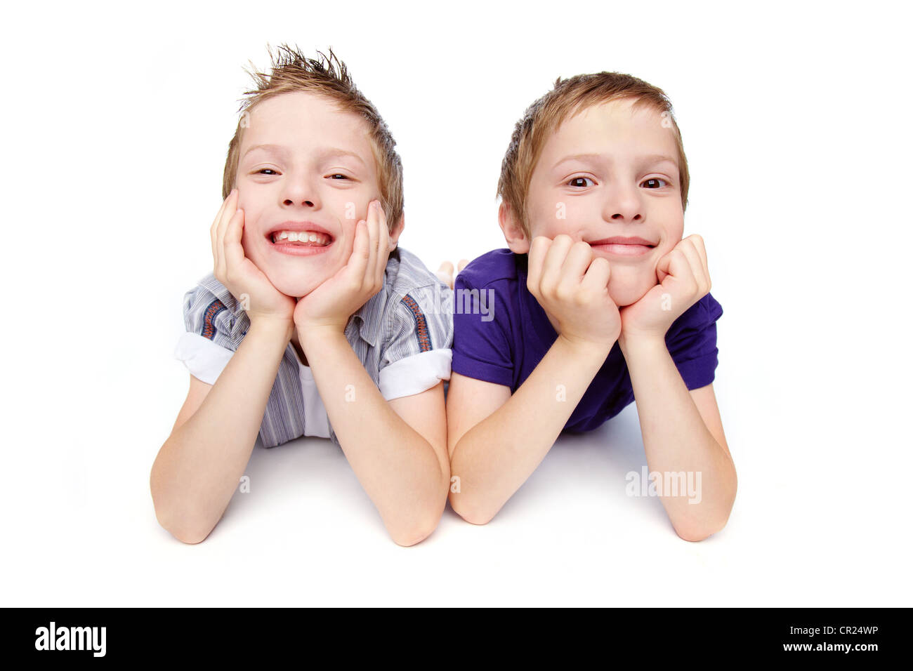 Cheerful brothers lying together, isolated against white background - Stock Image