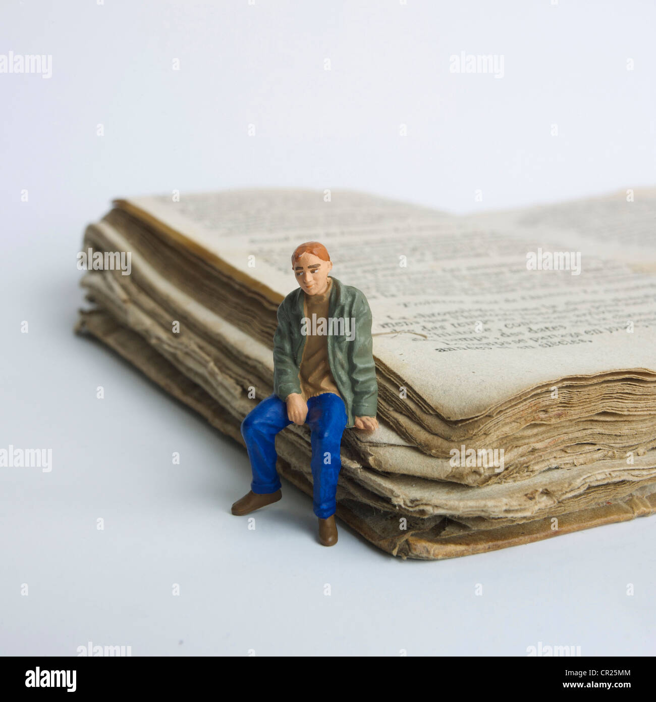 Young man / student miniature figurine, sitting on an old book - university / education / study / learning concept. - Stock Image