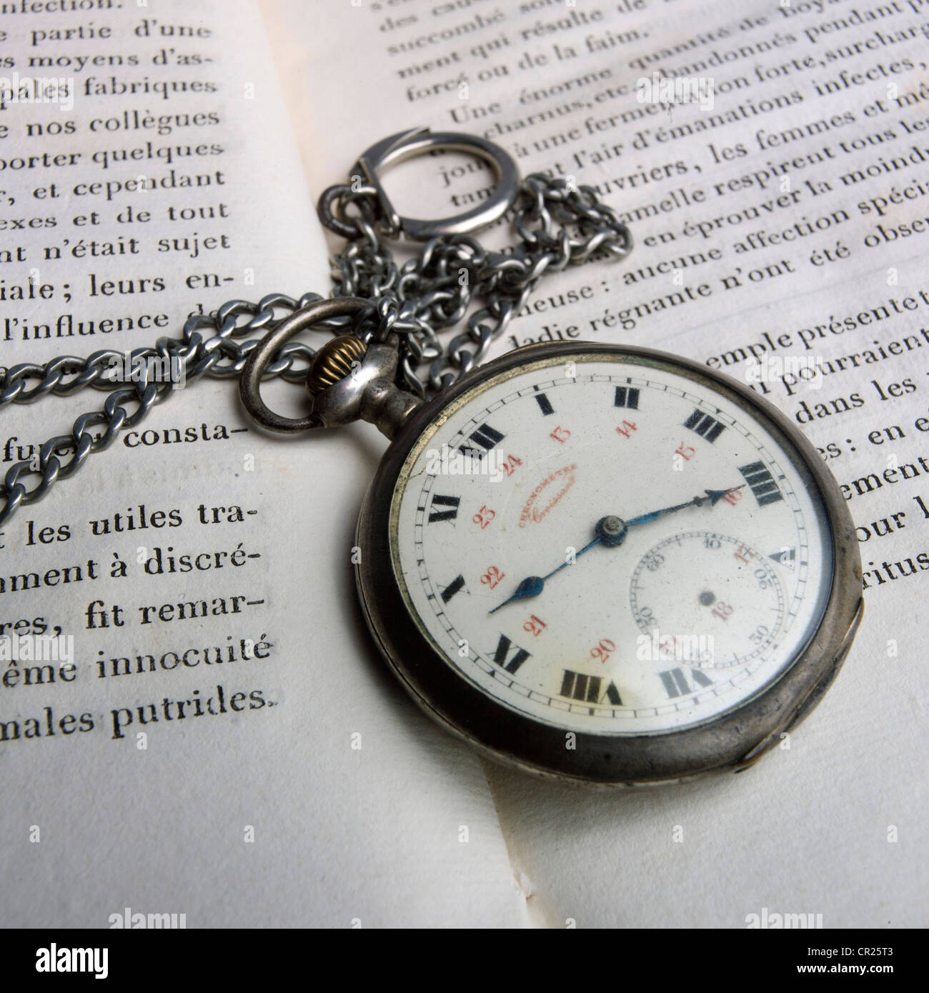 Pocket watch and open French book. - Stock Image