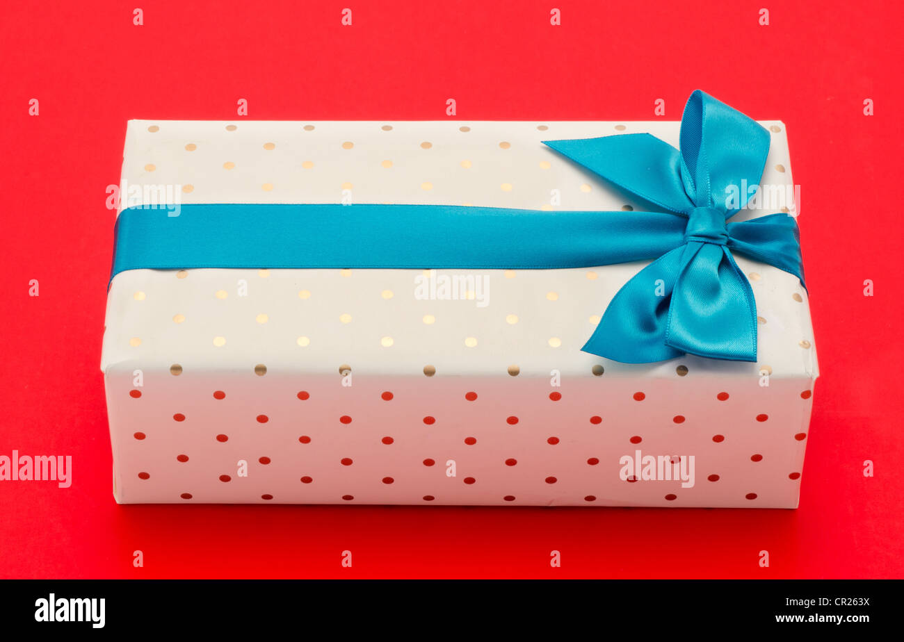 Gift wrapped box with a blue ribbon and bow - shot from above in the studio with a red background - Stock Image
