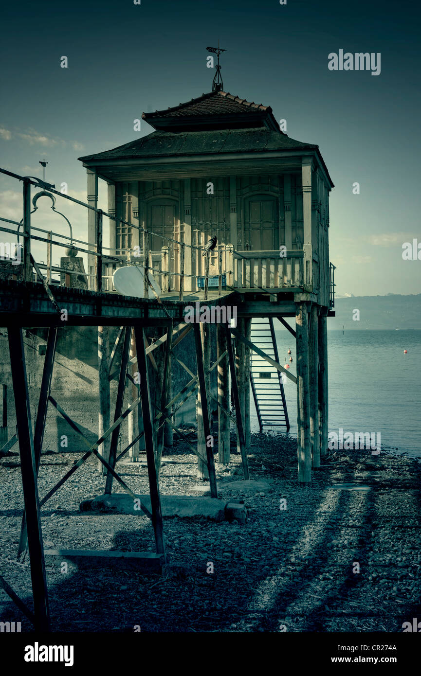 an old bath house on stilts on the banks of a lake - Stock Image
