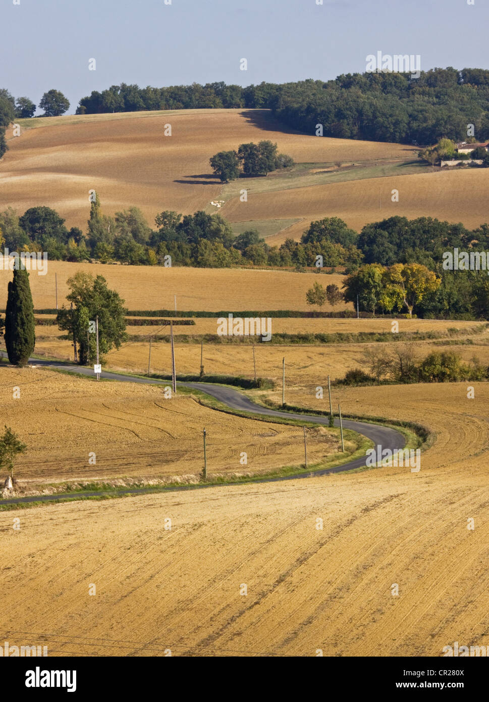 A minor rural road wending its way through a sparsely populated farming landscape in SW France in early autumn - Stock Image