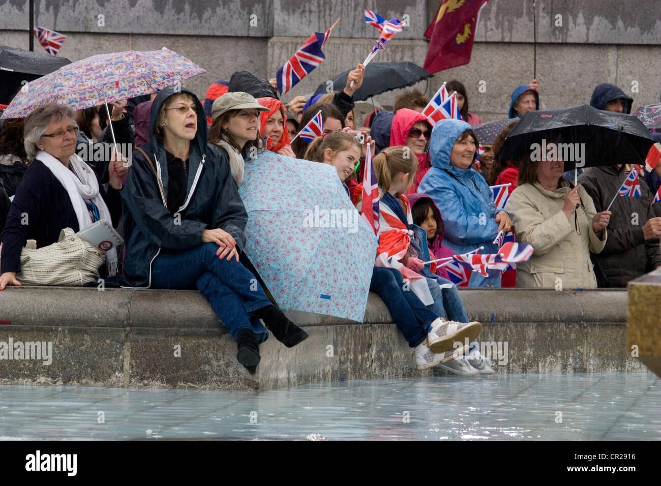 queens royal diamond jubilee 2012, revellers shelter in rain by fountain in trafalgar square London - Stock Image