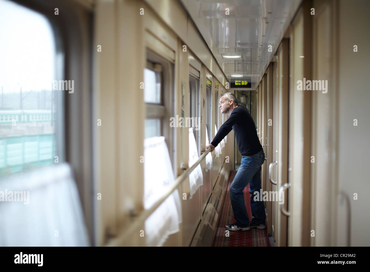 Adult man looking out of window on train - Stock Image
