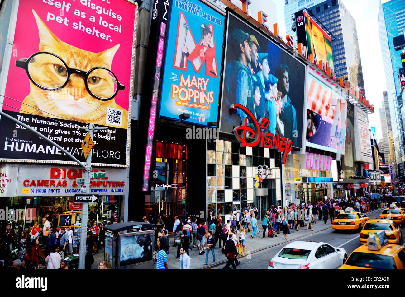Iconic New York yellow taxis in Times Square, Manhattan. Advertising boards for shows above Disney store Times square Stock Photo