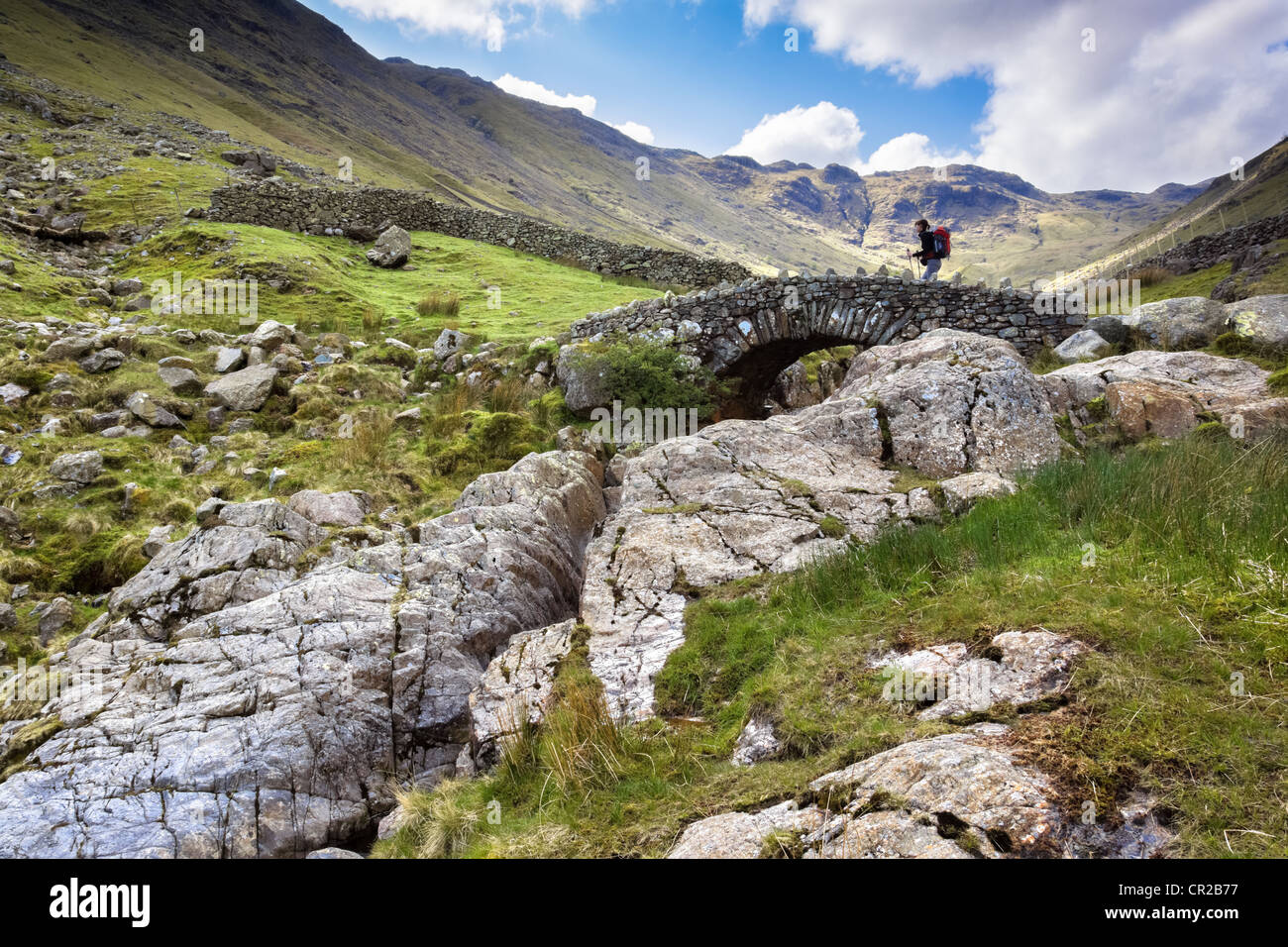 A hiker crosses Stockley Bridge on a bright spring day from Seathwaite Fell in the Lake District, Cumbria UK. Stock Photo