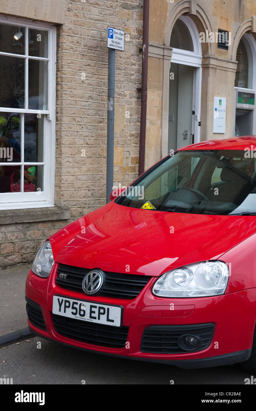 Red VW Golf with parking ticket fixed to windscreen parked under parking restriction sign - Stock Image