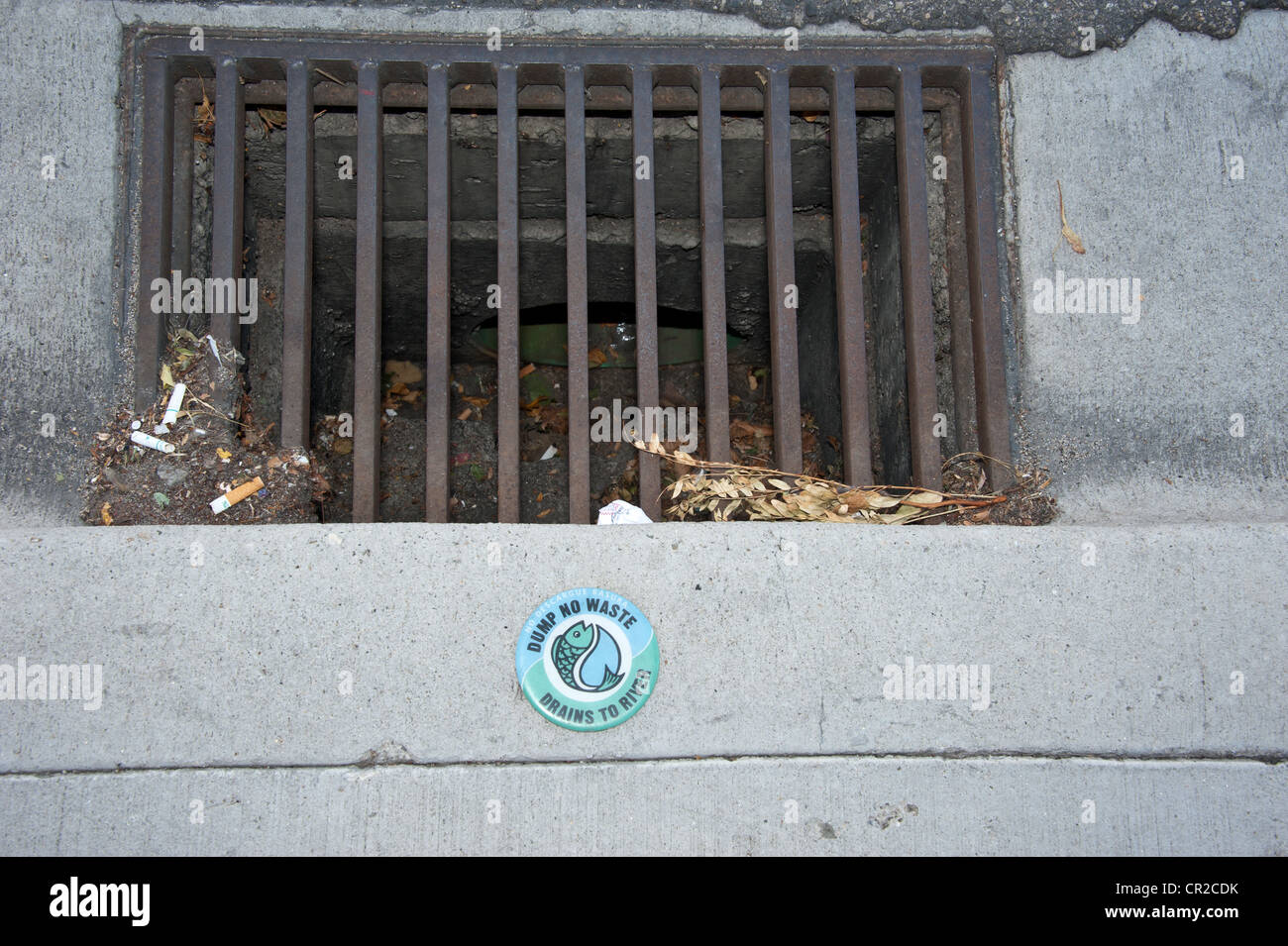 Storm drain in Boise, Idaho with a warning sign that informs people the water going down this drain goes directly - Stock Image