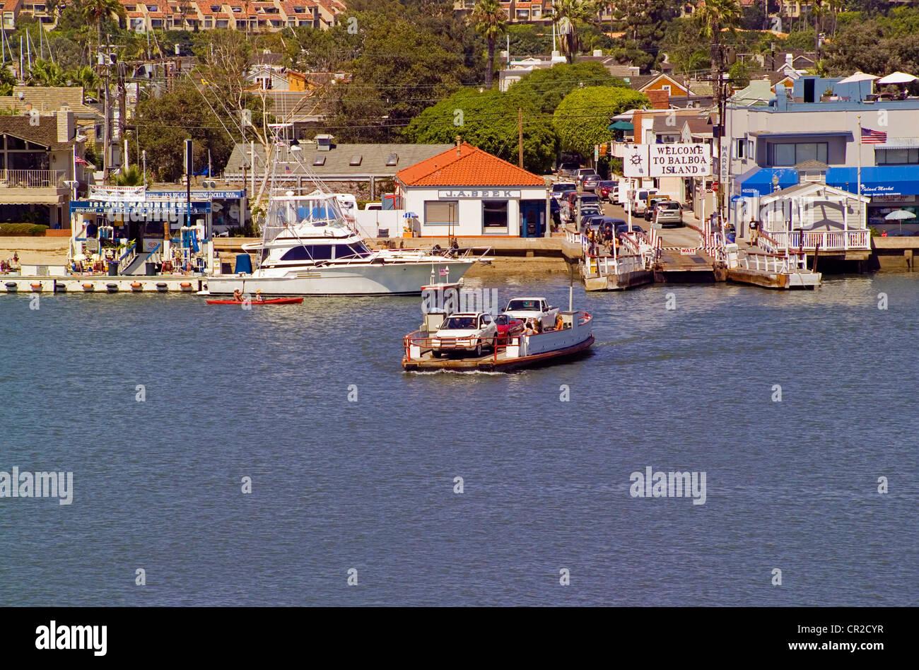 Historic three-car ferryboats cross Newport Harbor between the Fun Zone on the Balboa Peninsula and Balboa Island - Stock Image