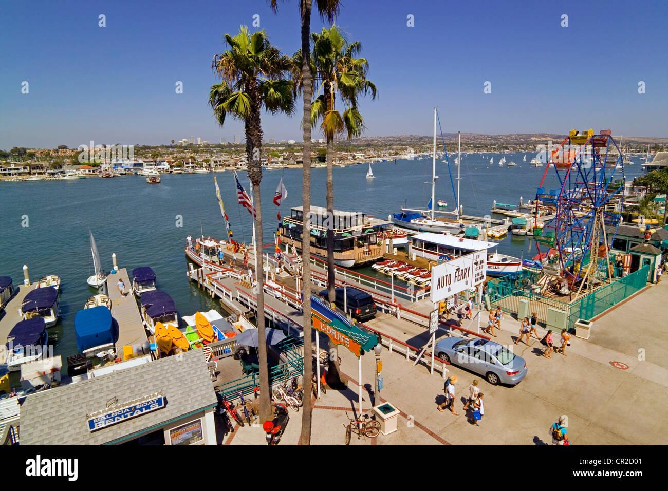 Vintage three-car ferryboats cross Newport Harbor between the Fun Zone on the Balboa Peninsula and Balboa Island - Stock Image