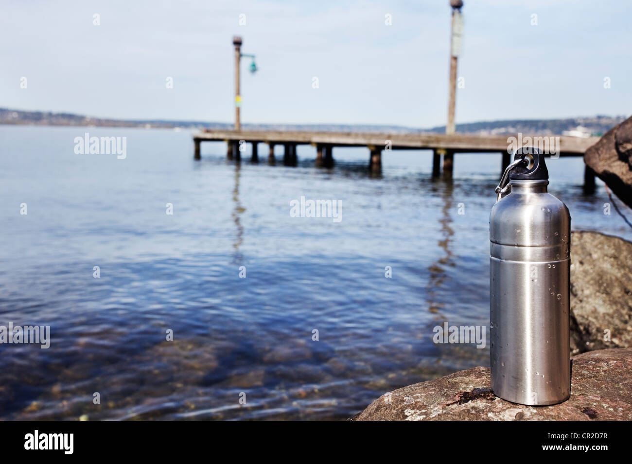 Reusable water bottle sitting by a clean lake - Stock Image