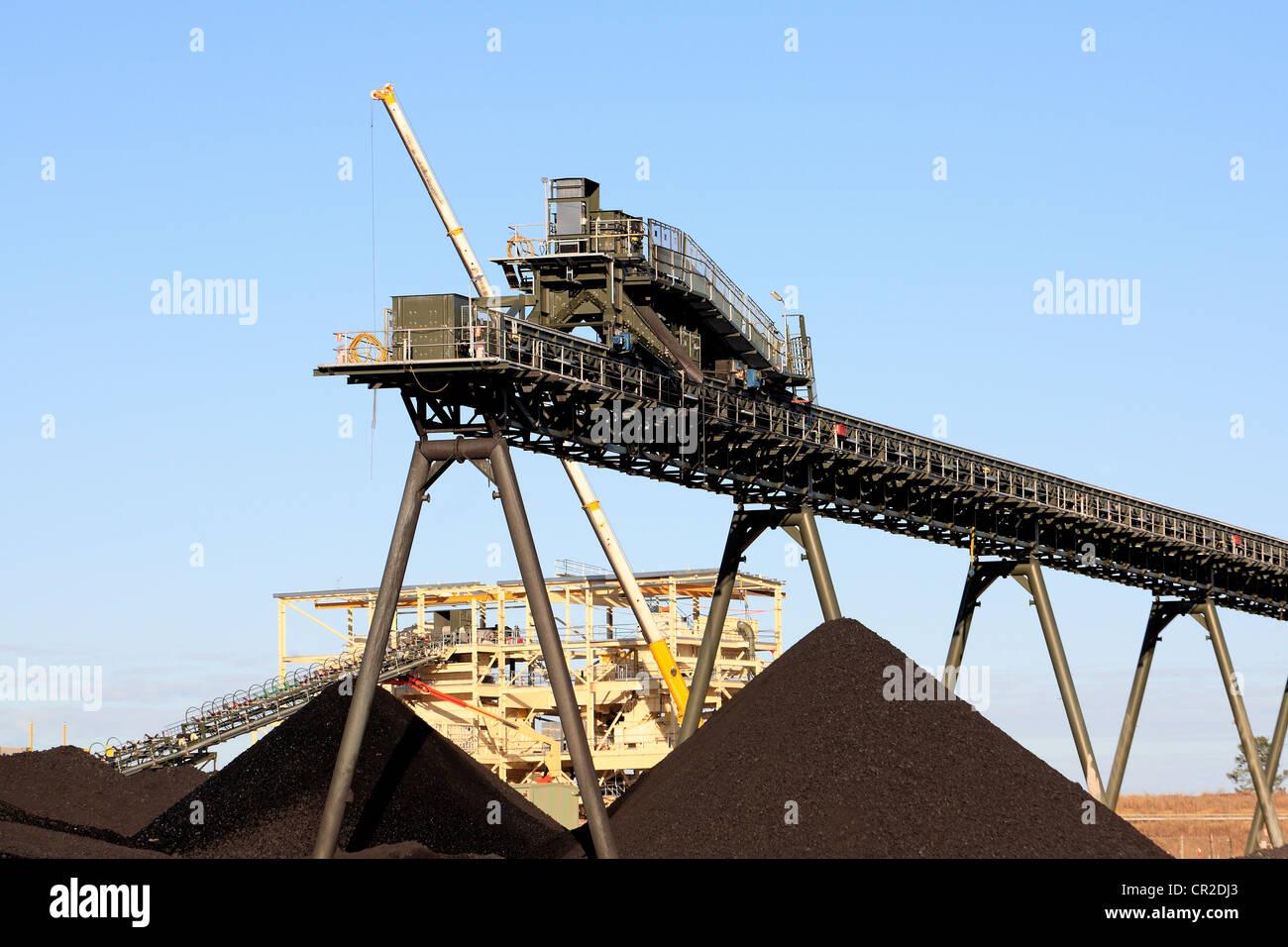 Coal Mining Conveyor Belt and piles of coal. - Stock Image