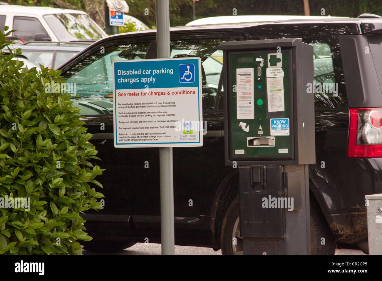 Disabled car parking charges sign in town center car park in Totnes, Devon, UK. - Stock Image