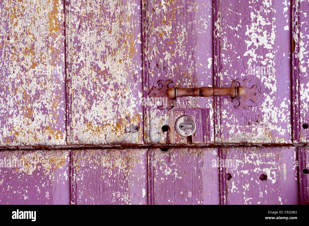Background Of An Old Painted, Crumbled Door. Handle On Purple Wooden Planks.