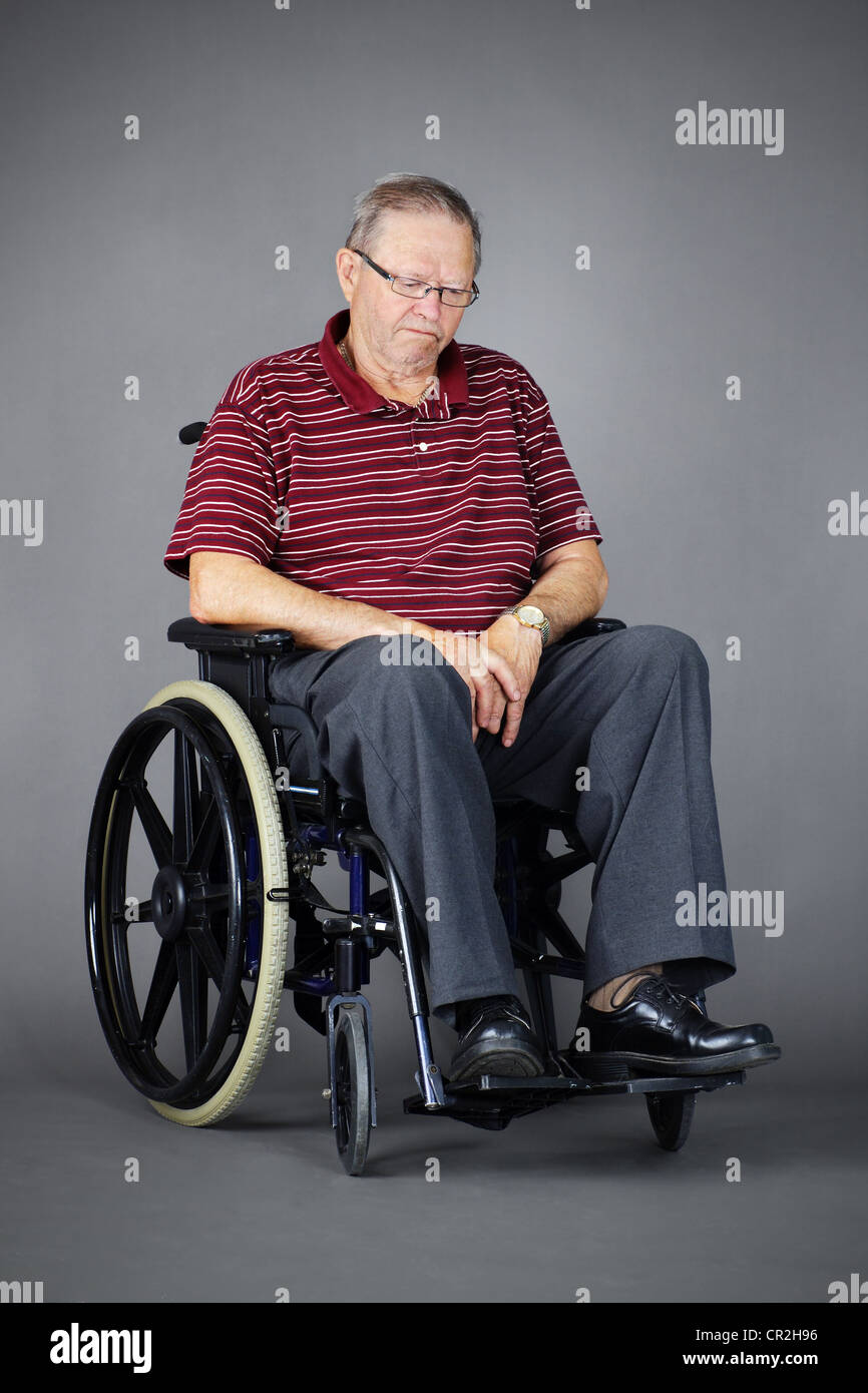 Sad or depressed senior man in a wheelchair, looking down, studio shot over grey background. - Stock Image
