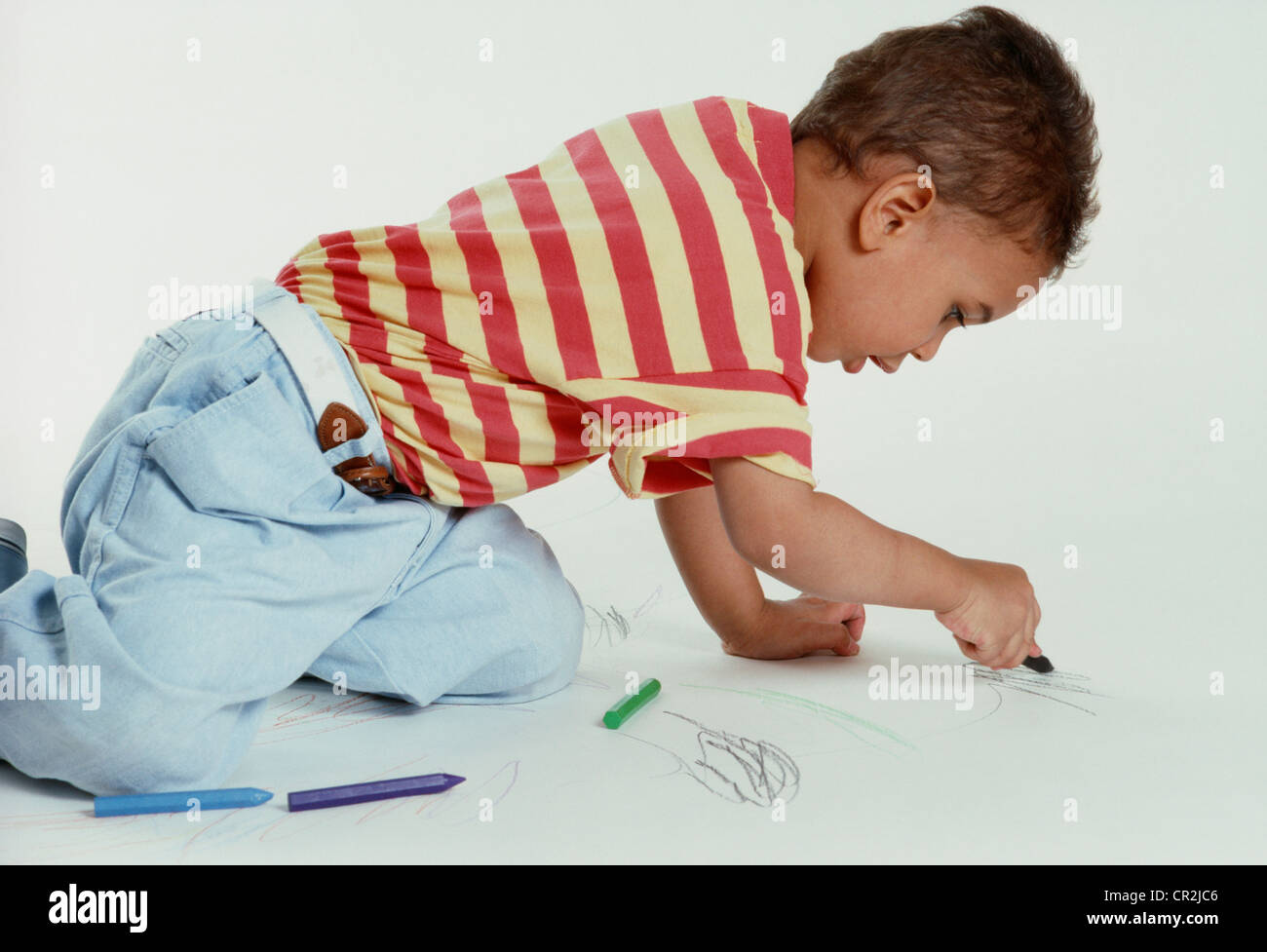 Three Year Old Mixed Race Boy Coloring With Crayons