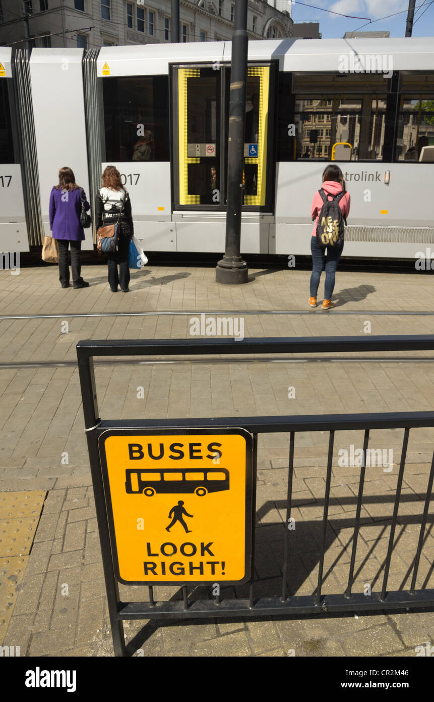 Transport interchange Picadilly Square Manchester with tram and warning sign - Stock Image