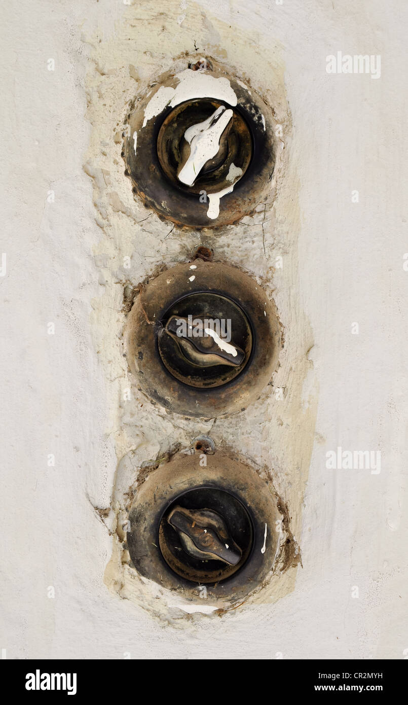 three vintage light switches in a row - Stock Image