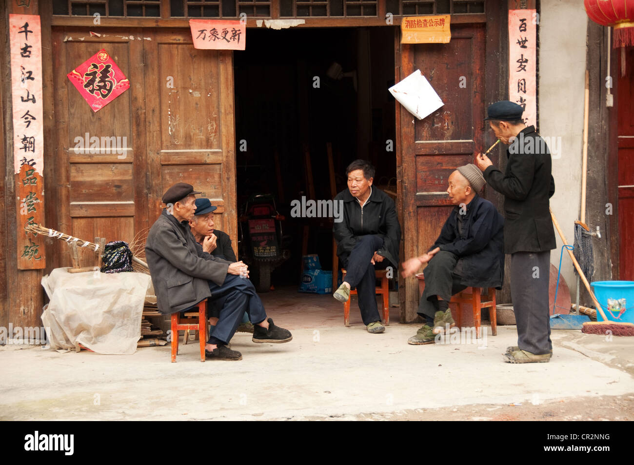 Elderly Dong men seated in front of a door, Zhaoxing Dong Village, China Stock Photo
