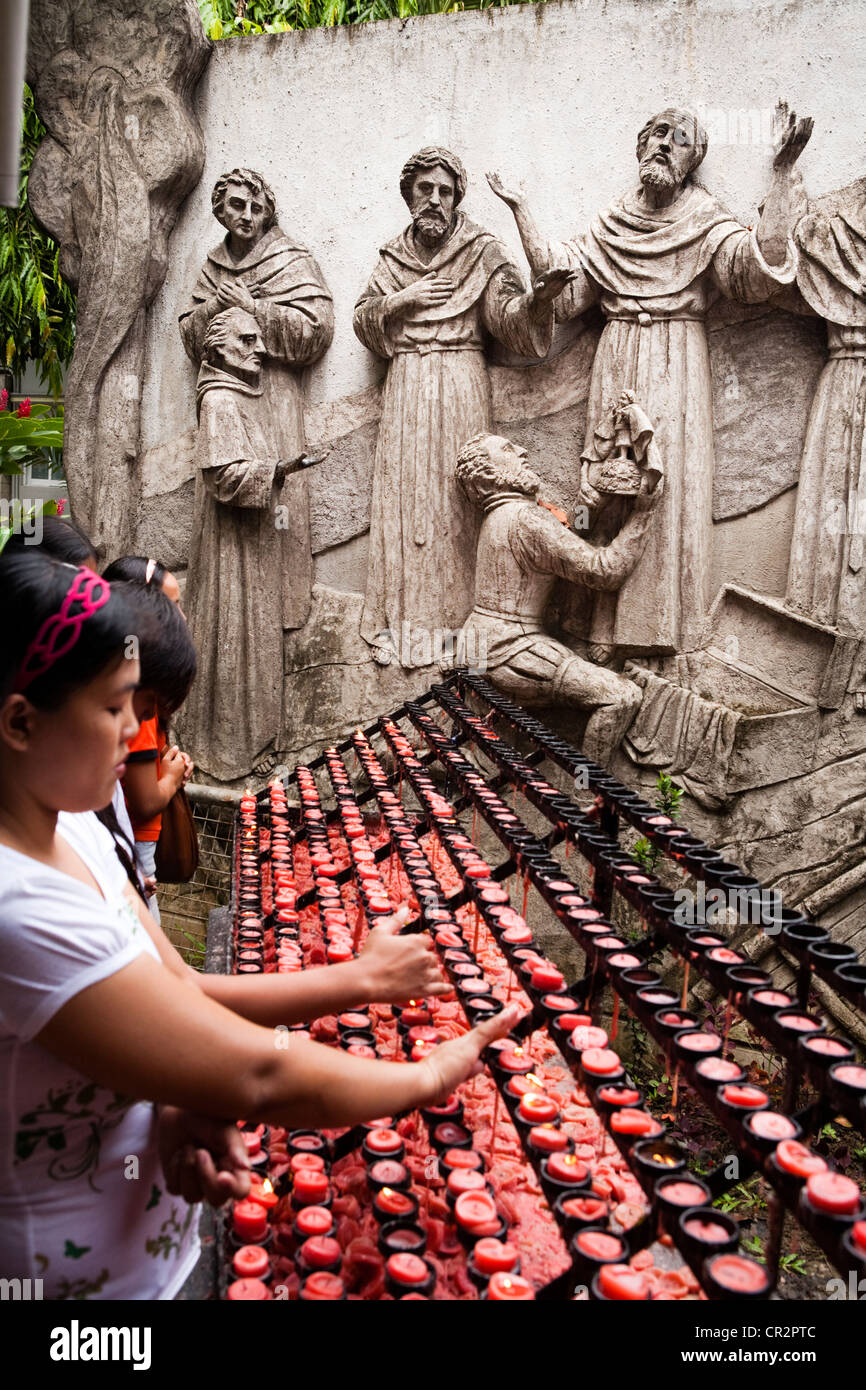 Filipinos lighting prayer candles during and after an outdoor sunday mass at The Minor Basilica of the Santo Nino, - Stock Image