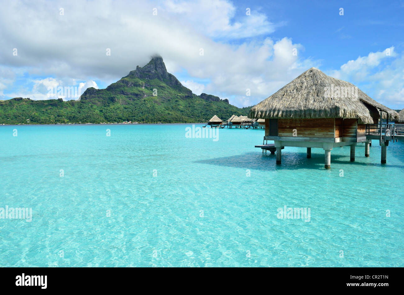 Luxury overwater bungalow in a vacation resort in the clear blue lagoon with a view on the tropical island of Bora - Stock Image