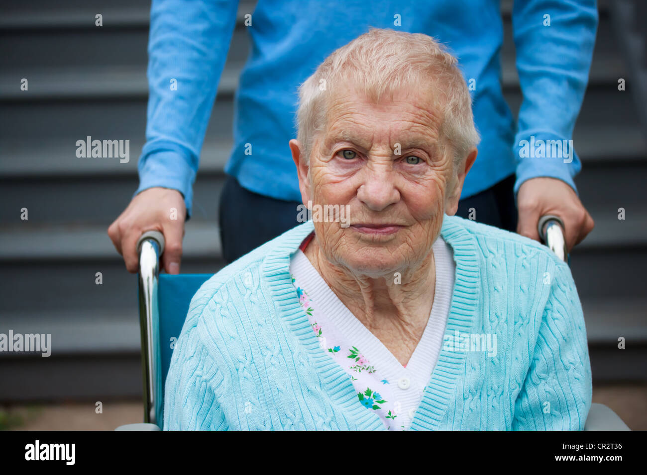 Senior Woman in Wheelchair with Assistant Behind her. - Stock Image