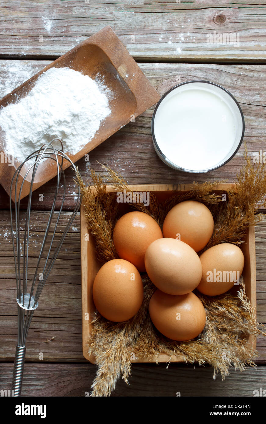 Eggs, flour, milk and whisk - Stock Image