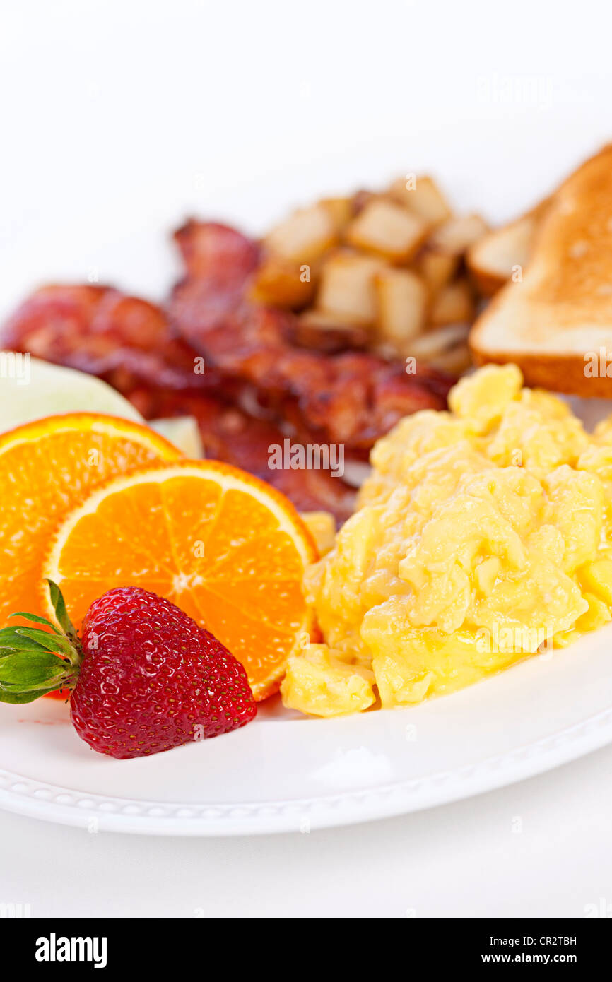 Delicious breakfast of scrambled eggs toast and bacon - Stock Image