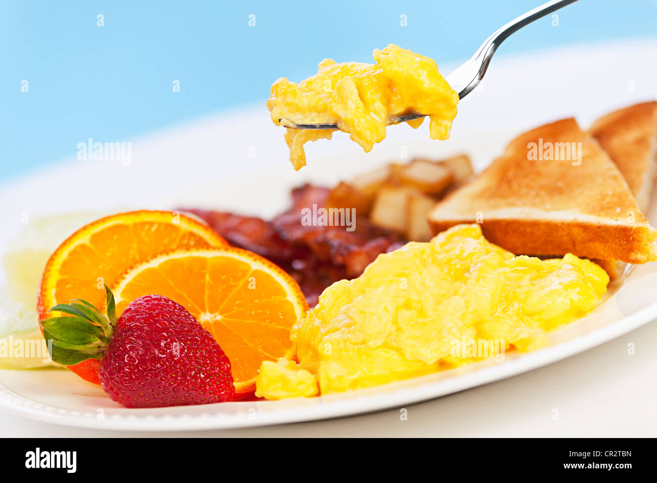 Scrambled eggs on a fork above breakfast plate with fruits toast and bacon - Stock Image